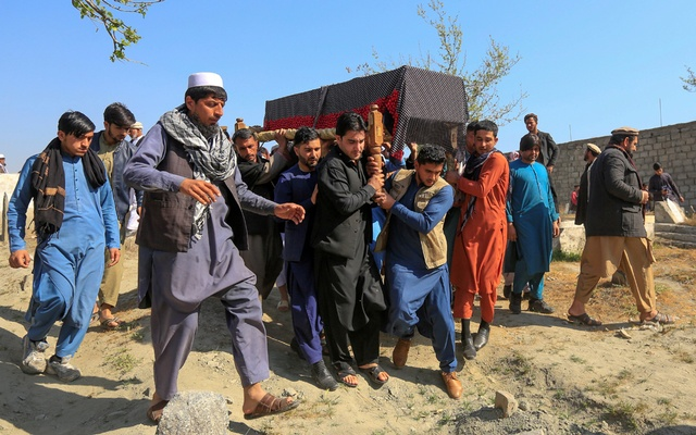 Afghan men carry the coffin of one of three female media workers who were shot and killed by unknown gunmen, in Jalalabad, Afghanistan Mar 3, 2021. REUTERS