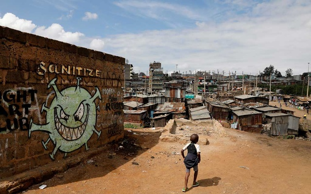 A boy walks in front of graffiti promoting the fight against the coronavirus disease (COVID-19) in the Mathare slums of Nairobi, Kenya, May 22, 2020. REUTERS