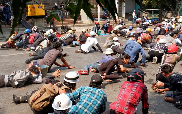 Protesters lie on the ground after police open fire to disperse an anti-coup protest in Mandalay, Myanmar, Mar 3, 2021. REUTERS