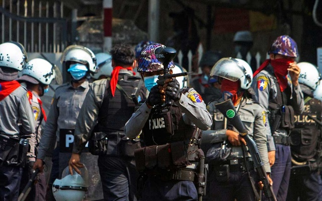 A riot police officer fires a rubber bullet toward protesters during a protest against the military coup in Yangon, Myanmar, Feb 28, 2021. REUTERS