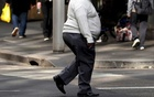 A man crosses a main road as pedestrians carrying food walk along the footpath in central Sydney, Australia. Reuters
