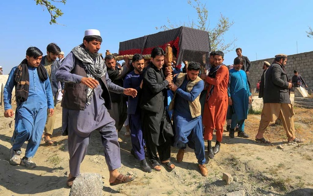 Afghan men carry the coffin of one of three female media workers who were shot and killed by unknown gunmen, in Jalalabad, Afghanistan March 3, 2021. REUTERS