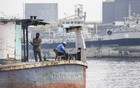 A security guard says his prayers on a cargo vessel as a ship-breaker works next to him on the bank of the Buriganga river at Munshikhola in Dhaka's Shyampur. Photo: Asif Mahmud Ove