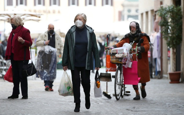 People walk near the open-air market as the government is due to announce stricter coronavirus disease (COVID-19) restrictions, in Rome, Italy, March 12, 2021. REUTERS