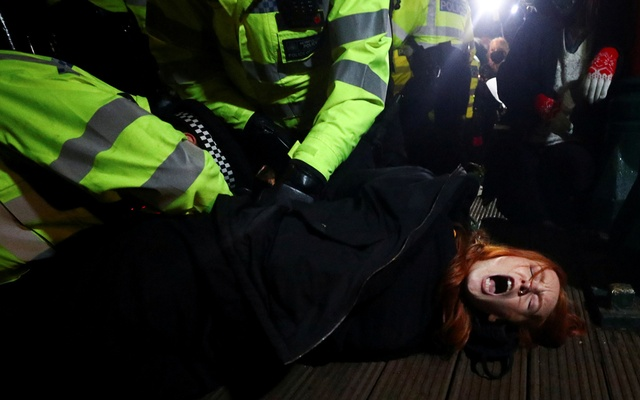 Police detain a woman as people gather at a memorial site in Clapham Common Bandstand, following the kidnap and murder of Sarah Everard, in London, Britain March 13, 2021. REUTERS