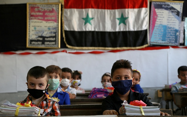 Students wearing protective face masks sit in a classroom as a school year kicks off amid concerns about the spread of the coronavirus disease (COVID-19), in Damascus, Syria Sept 13, 2020. REUTERS