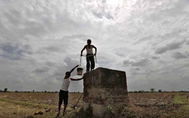Farmers are pictured under monsoon clouds as they clean a canal water tank at Shantipura village in Gujarat Jul 2, 2014. REUTERS