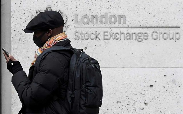 A man wearing a protective face mask walks past the London Stock Exchange Group building in the City of London financial district, whilst British stocks tumble as investors fear that the coronavirus outbreak could stall the global economy, in London, Britain, March 9, 2020. REUTERS