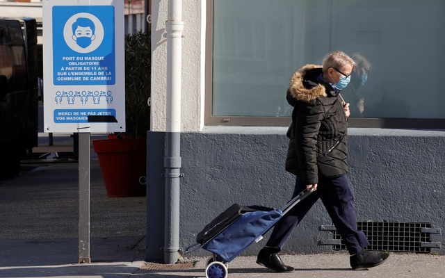 A woman, wearing a protective face mask, walks with her shopping trolley in a street in Cambrai before new lockdowns imposed during a month-long on Paris and parts of the north after a faltering vaccine rollout and spread of highly contagious coronavirus disease (COVID-19) variants in France, Mar 19, 2021. REUTERS