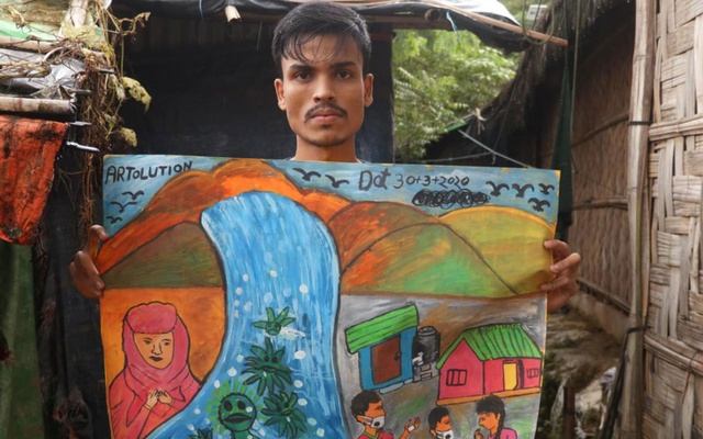 A photo provided by S M Suza Uddin, via Artolution, Mohammed Nur with his coronavirus-themed artwork at the Balukhali refugee camp in Bangladesh, Aug. 4, 2020. (S M Suza Uddin, via Artolution via The New York Times)