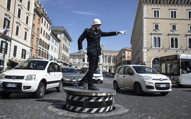 A veteran traffic officer, Pierluigi Marchionne, directs traffic on the Piazza Venezia in Rome, March 18, 2021. The New York Times