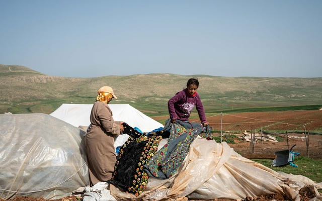Fadwa Abu Awad, a Palestinian herder, and her daughter Tasneem sort through belongings protected by plastic sheets in the West Bank hamlet of Humsa, where the Israeli army has repeatedly dismantled homes and residents have repeatedly rebuilt them, March 10, 2021. (Samar Hazboun/The New York Times)