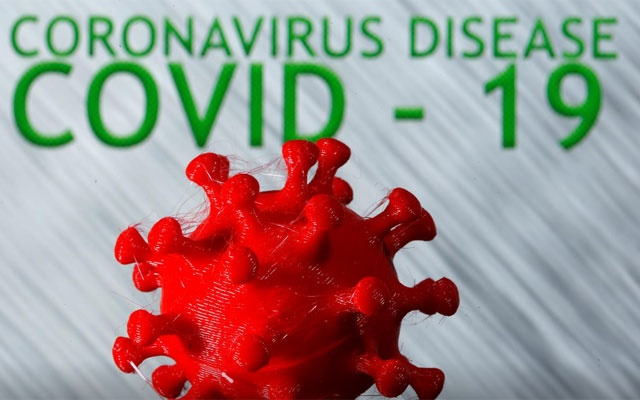 A 3D-printed coronavirus model is seen in front of the words coronavirus disease (COVID-19) on display in this illustration taken March 25, 2020. REUTERS