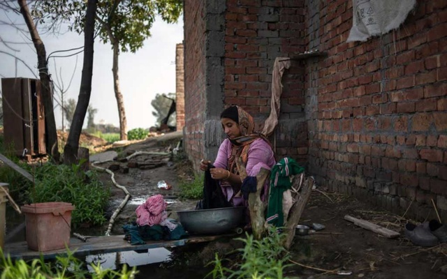 Rajwinder Kaur, 28, washes laundry at her home in Baghwanpura, India, on Feb. 26, 2021. Kaur, a widow, works a half-acre farm. (Rebecca Conway/The New York Times)