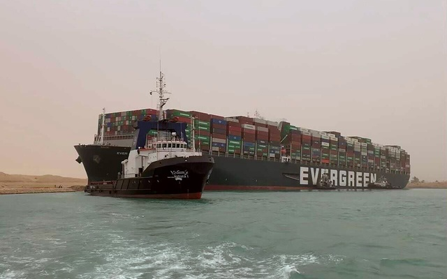 In a photo from the Suez Canal Authority, a boat navigates in front of the Ever Given, a container ship operated by a company called Evergreen, which has blocked all traffic in the Suez Canal when it became wedged there. The shutdown of the vital waterway and its impact on trade underscore the world's reliance on global supply chains. Suez Canal Authority via The New York Times