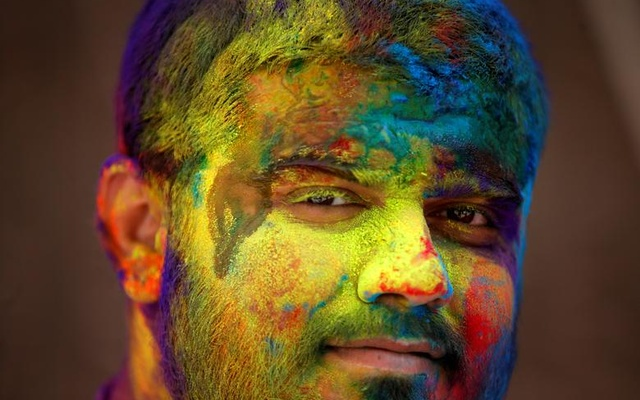 A man daubed in colours looks on during Holi celebrations in Ahmedabad, India, March 29. Reuters