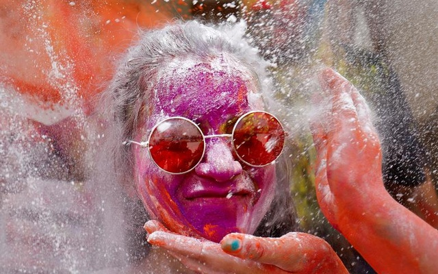 A woman reacts as powder is applied to her face on during Holi celebrations in Ahmedabad, India, March 29. Reuters