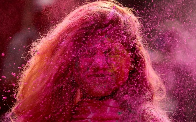 A woman daubed in colours reacts as powder is thrown towards her during Holi celebrations in Chennai, India, March 29. Reuters