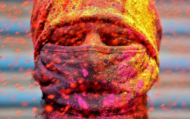 A man wearing a protective face mask reacts as colour powder is thrown towards him during Holi celebrations in Chennai, India, March 29. Reuters