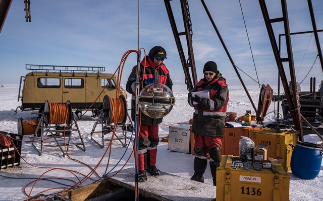 Scientists register a light-detecting sphere, one of 36 to be submerged 2,300 feet below the surface of Lake Baikal in Russia, on Monday March 1, 2021. The New York Times