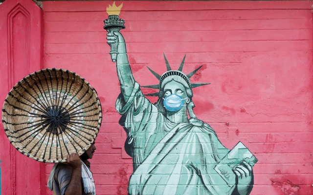 A man carrying a basket walks past a graffiti depicting the Statue of Liberty wearing a mask, amidst the spread of the coronavirus disease (COVID-19), on a street in Mumbai, India, March 30, 2021. REUTERS/Francis Mascarenhas