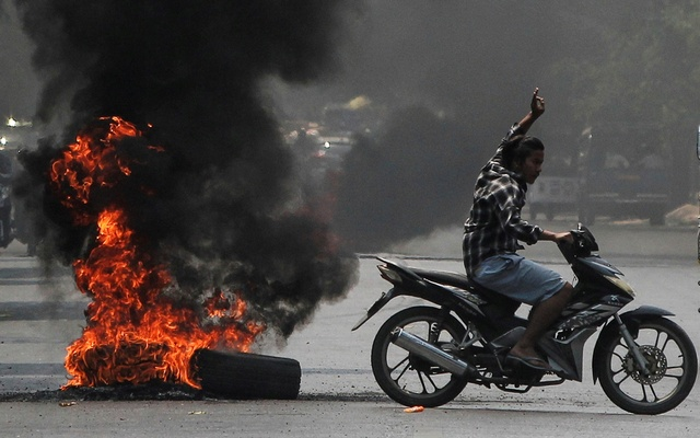 A man flashes the three-finger salute as he passes burning tires during a protest against the military coup, in Mandalay, Myanmar April 1, 2021. REUTERS