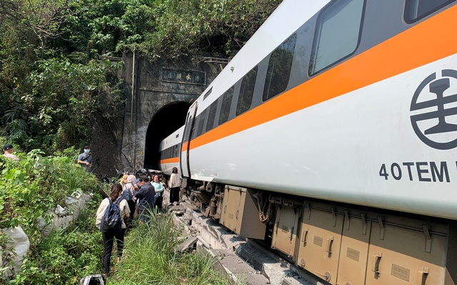 People walk next to a train which derailed in a tunnel north of Hualien, Taiwan April 2, 2021, in this handout image provided by Taiwan's National Fire Agency. REUTERS