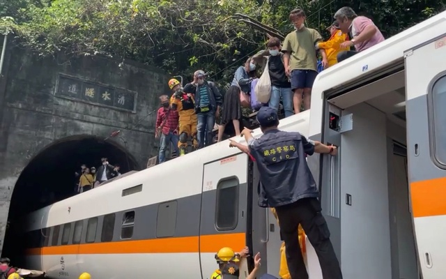Rescue team help stranded passengers down from the roof of a train which derailed in a tunnel north of Hualien, Taiwan Apr 2, 2021. REUTERS