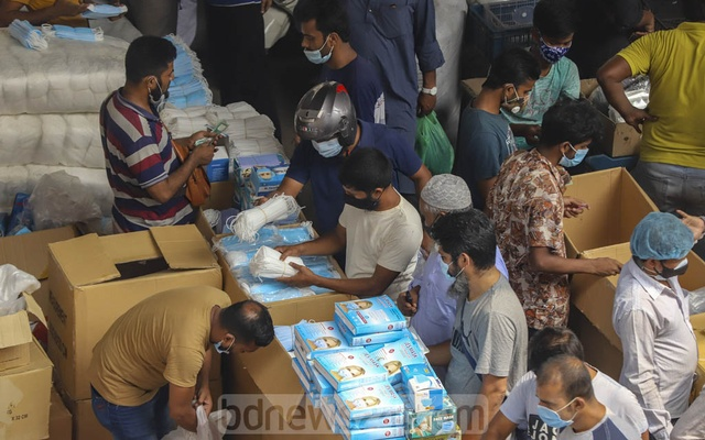Customer check masks at the wholesale market below the Second Buriganga Bridge in Dhaka's Babubazar on Saturday, Apr 3, 2021 as demand and prices soared after the government decision to impose a lockdown over a new wave of coronavirus infections. Photo: Asif Mahmud Ove