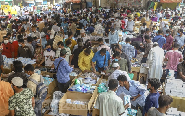 Customers crowd the wholesale market of masks below the Second Buriganga Bridge in Dhaka's Babubazar on Saturday, Apr 3, 2021 after the government decided to lock Bangladesh down over the coronavirus resurgence. Photo: Asif Mahmud Ove