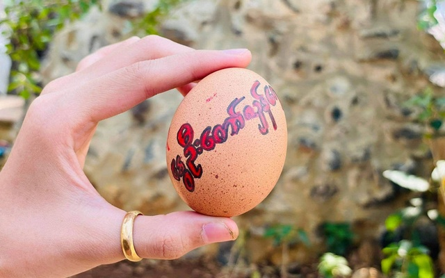 A person shows a painted Easter egg with a sign reading