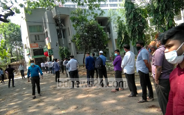 Customers wait in long queues outside the Agrani bank branch at the National Press Club in Dhaka on Monday, Apr 5, 2021 as the government reduced transaction hours amid a coronavirus lockdown.