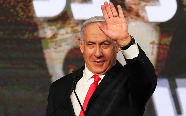 Israeli Prime Minister Benjamin Netanyahu gestures as he delivers a speech to supporters following the announcement of exit polls in Israel's general election at his Likud party headquarters in Jerusalem Mar 24, 2021. REUTERS