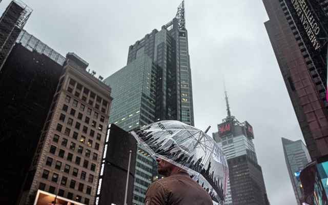 A man stands amid the mostly-darkened skyscrapers of midtown Manhattan on March 18, 2021. New York's economic downturn has led state leaders to agree to new taxes on the wealthy. The New York Times