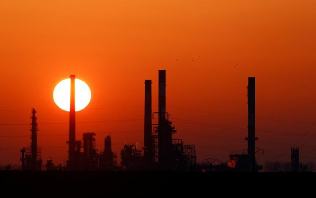 The sun sets behind the chimneys of the Total Grandpuits oil refinery, southeast of Paris, France, March 1, 2021. REUTERS