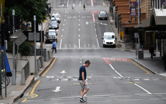 A man crosses a mostly empty city centre street as people in Greater Brisbane have been ordered into lockdown as authorities try to suppress a growing coronavirus disease (COVID-19) cluster in Brisbane, Australia, Mar 30, 2021. REUTERS