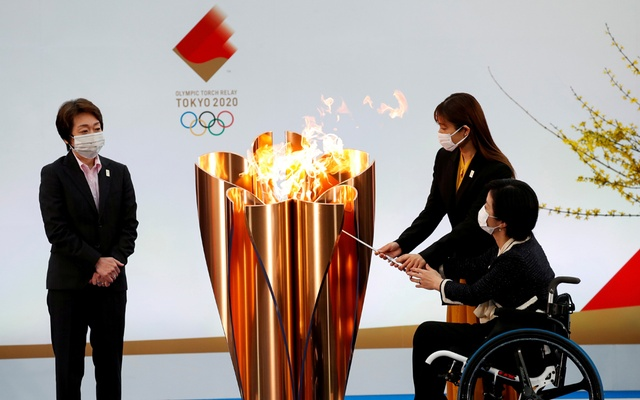 Tokyo 2020 President Seiko Hashimoto looks on as actor Satomi Ishihara and Paralympian Aki Taguchi light the celebration cauldron on the first day of the Tokyo 2020 Olympic torch relay in Naraha, Fukushima prefecture, Japan March 25, 2021. REUTERS