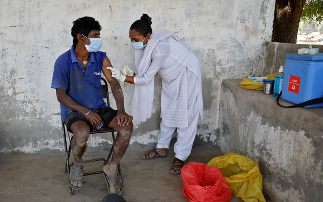 A brick kiln worker receives a dose of COVISHIELD, a coronavirus disease (COVID-19) vaccine manufactured by Serum Institute of India, at Kavitha village on the outskirts of Ahmedabad, India, April 8, 2021. Reuters