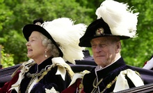 Britain's Queen Elizabeth II and Prince Phillip, the Duke of Edinburgh, wearing their Order of the Garter robes, ride in an open-topped carriage to Windsor Castle following the Garter Ceremony, Jun 18, 2001. REUTERS