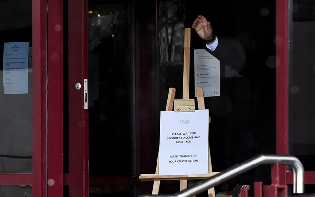 Hotel staff gestures at the entrance of Crowne Plaza Dublin Airport Hotel, as Ireland introduces hotel quarantine programme for 'high-risk' countries' travellers, in Dublin, Ireland March 26, 2021. Reuters