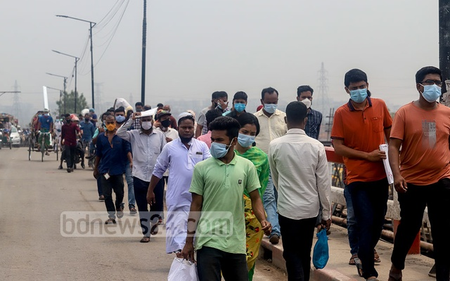 Commuters cross a bridge in Dhaka's Aminbazar on foot to reach their destinations on Saturday, Apr 10, 2021, amid an exodus from the capital ahead of a new lockdown with stricter rules scheduled to start from Apr 14. Photo: Asif Mahmud Ove