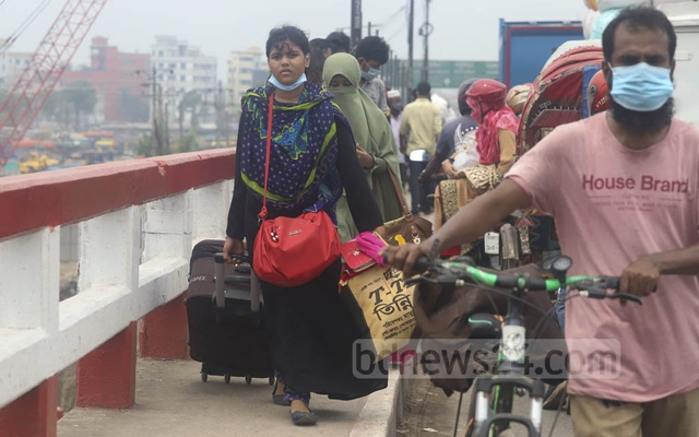 A woman walks to cross the Amin Bazar bridge on Saturday Apr 10, 2021 as buses are banned from entering or leaving the cities. Photo: Asif Mahmud Ove