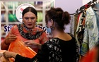 Jiya, 35, a transgender woman and tailor, talks with a customer at her shop in Karachi, Pakistan April 5, 2021. REUTERS