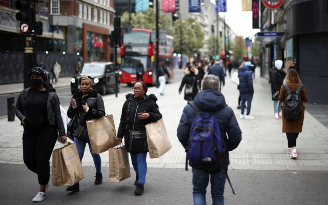 People walk on Oxford street, as the coronavirus disease (COVID-19) restrictions ease, in London, Britain Apr 12, 2021. REUTERS