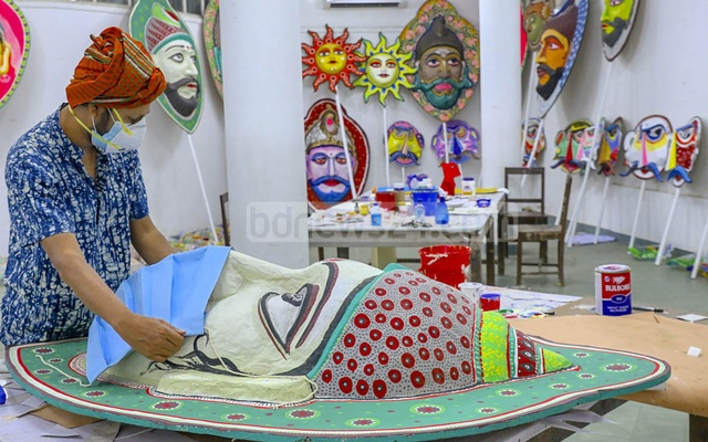 An artist putting a face mask on a mask prepared for Mangal Shobhajatra procession of Pahela Baishakh, but the authorities cancelled the event due to the coronavirus outbreak saying the masks and other items made for the procession will be displayed via electronic media.