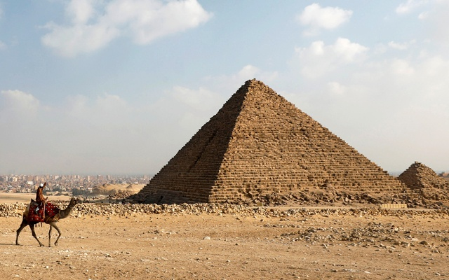 A camel guide waits for customers next to the pyramid of Khafre or