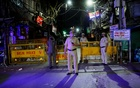 Police officers stand guard on a deserted street during a curfew to limit the spread of the coronavirus disease (COVID-19), in New Delhi, April 6, 2021. REUTERS
