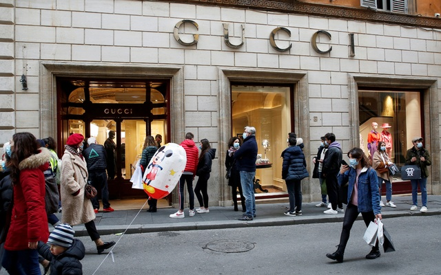 People queue outside a Gucci store on via Condotti in Rome, Italy December 19, 2020. REUTERS
