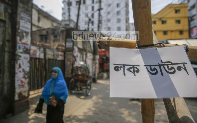 People move along a lockdown sign on barricades at the entrance of Golapbagh in Dhaka on the second day of a coronavirus lockdown on Thursday, Apr 15, 2021. Photo: Mahmud Zaman Ovi