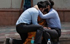 A woman is consoled by her children after her husband died due to the coronavirus disease (COVID-19) outside a mortuary of a COVID-19 hospital in New Delhi, India, April 15, 2021. Reuters
